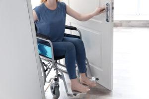 Jeune femme en fauteuil ouvrant la porte