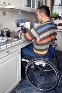Homme en fauteuil utilisant des plaques de cuisson