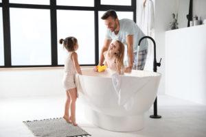 jeune père avec ses filles prennant leur bain