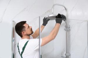 technicien installant la robinetterie douche