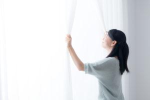 femme ouvrant la fenêtre